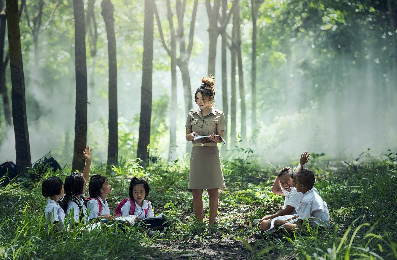 a teacher and her students having class in the woods